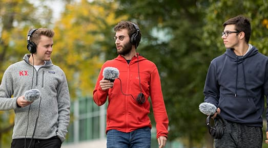 Student walk around campus with microphones